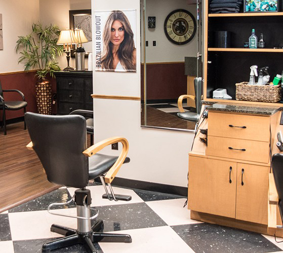 Hair stylist's workplace with adjustable chair, wall mirror, and a shelving unit filled with products and tools